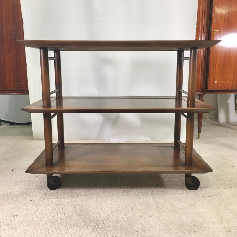 1950s three-tier walnut serving cart on casters. 11.5 inches height between tiers allowing for bottles to stand.