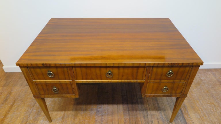Midcentury tiger wood desk. Italian midcentury desk of tiger wood having five drawers solid brass hardware. The desk has a glass top also to protect the beautiful top. In good condition solid and sturdy, having some dings and ware to the legs, sides