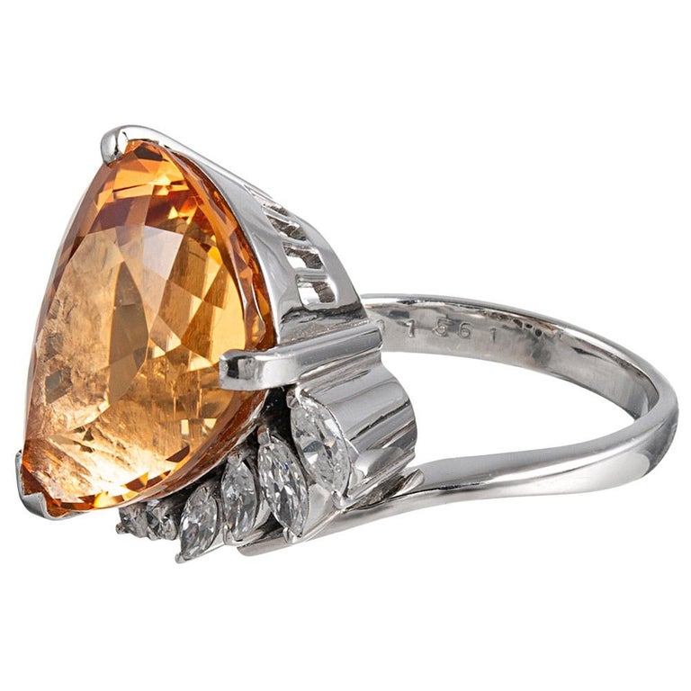 A 15.61 carat pear brilliant topaz is flattered by its platinum mounting with a tapered row of round and marquis diamonds. The asymmetric design is unusual and well-proportioned, allowing the ring to sit comfortably on the finger. The diamonds weigh