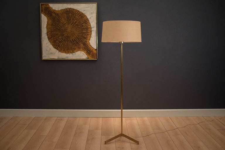 Mid century brass floor lamp in the manner of Paul McCobb. This tripod lamp includes a milk glass cone shade underneath the original drum shade.
