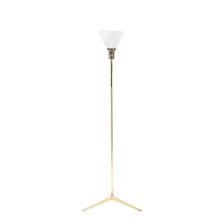 This elegant Mid-Century Modern floor lamp was designed by Paul McCobb in the United States circa 1950. It features an atomic tripod base with a cylindrical body all in polished brass. The lamp culminates in a domed textured white glass shade. This