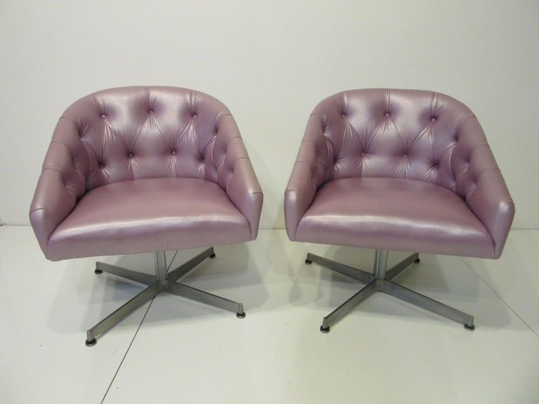 A pair of tufted chairs in a iridescent lavender original special order leatherette with cast aluminum swiveling star bases and domes of silent foot pads . Retains the original label to the bottom from the Shelby Williams Mfg. Company .