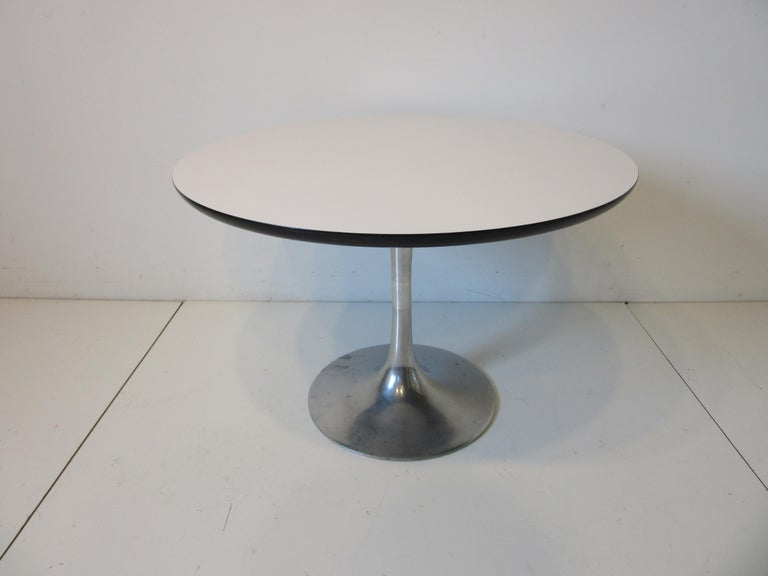 A smaller mid sized tulip side / lamp table with cast aluminum base and round white laminate top with black  designed by Maurice Burke and manufactured by the Burke furniture company.