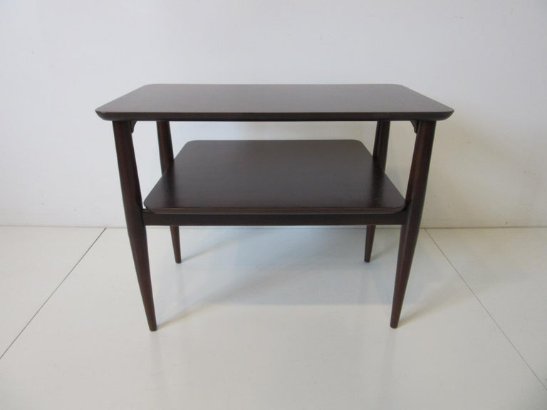 A nice sized midcentury two-tiered wood side table with beveled edges and conical legs refinished in a rich ebony tone giving the piece a very high stylish feel. The perfect table to share between two lounge chairs or able to stand alone.