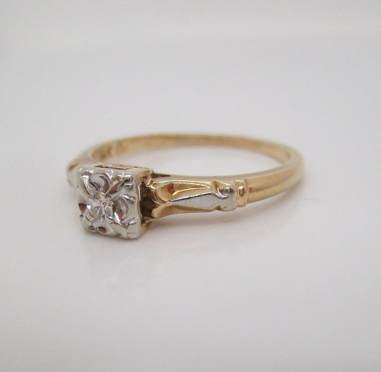 This is a beautiful mid-century engagement ring in 14k yellow and white gold with a brilliant white single cut diamond center stone! The ring has a classic mid-century look with a yellow gold shank and a bright white gold illusion head with an