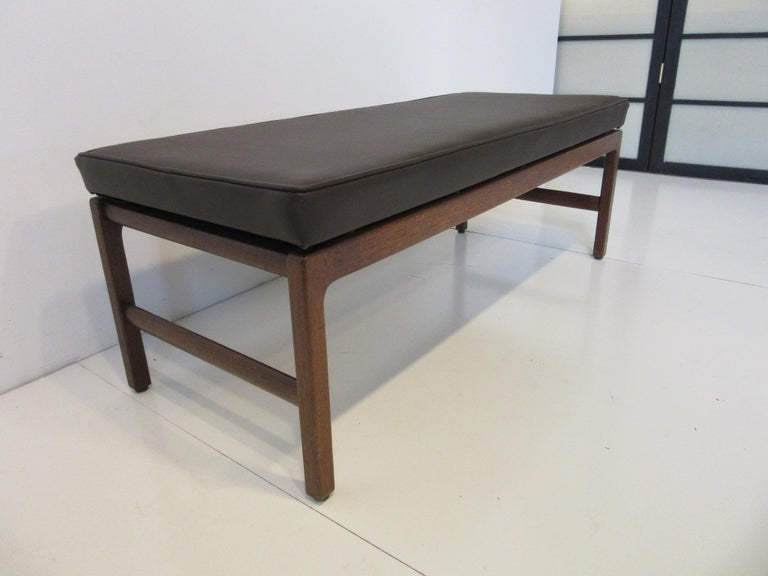 A walnut based upholstered bench with floating seat in dark brown leatherette manufactured in the manner of Jens Risom.