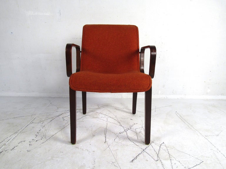 A stylish set of 4 midcentury upholstered dining chairs. Bentwood frames with interestingly contoured armrests on each chair. Seats and backs are covered in a vintage orange upholstery. This set is sure to provide a great seating solution to any