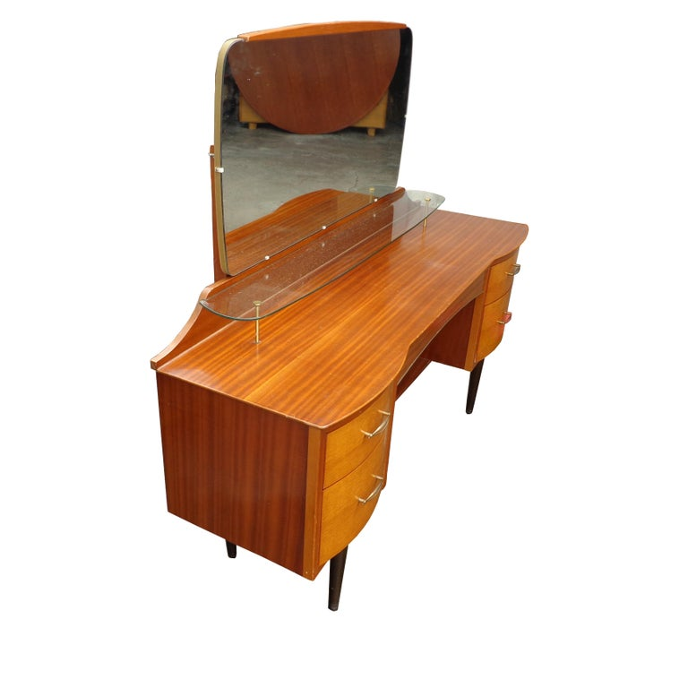 Mid century vanity dresser with mirror  Charming teak bow front dresser with 4 drawers and an extra glass shelf for display. Brass pulls.