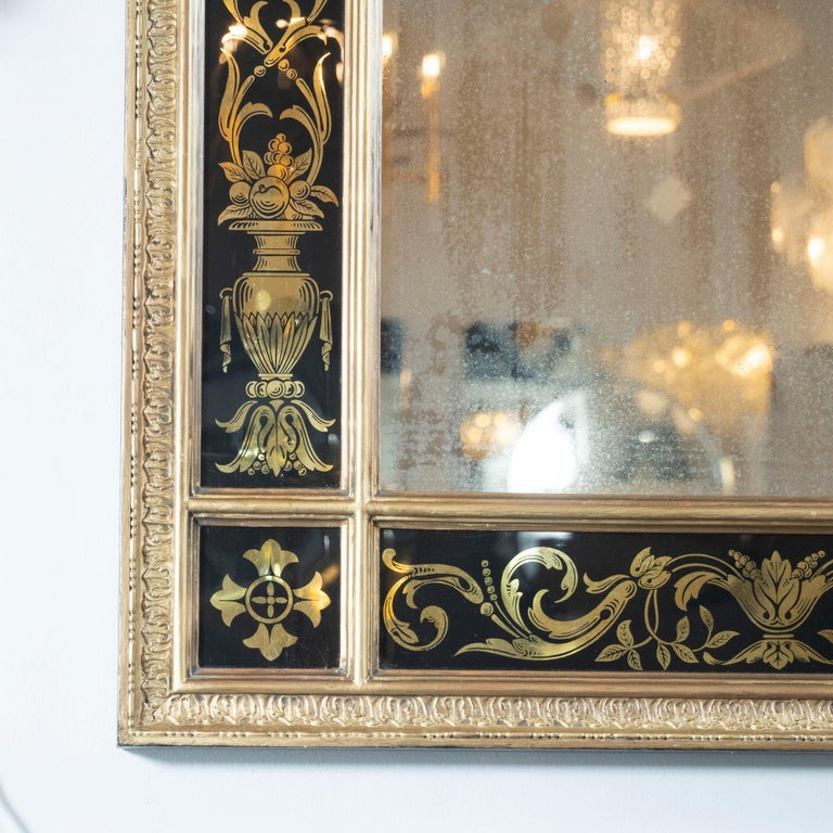 This elegant Mid-Century Modern Venetian wall mirror was realized in Italy, circa 1950. It features a filigreed gilded frame with reverse églomisé offering foliate and figurative motifs against a black background with rectangular plain mirror in the
