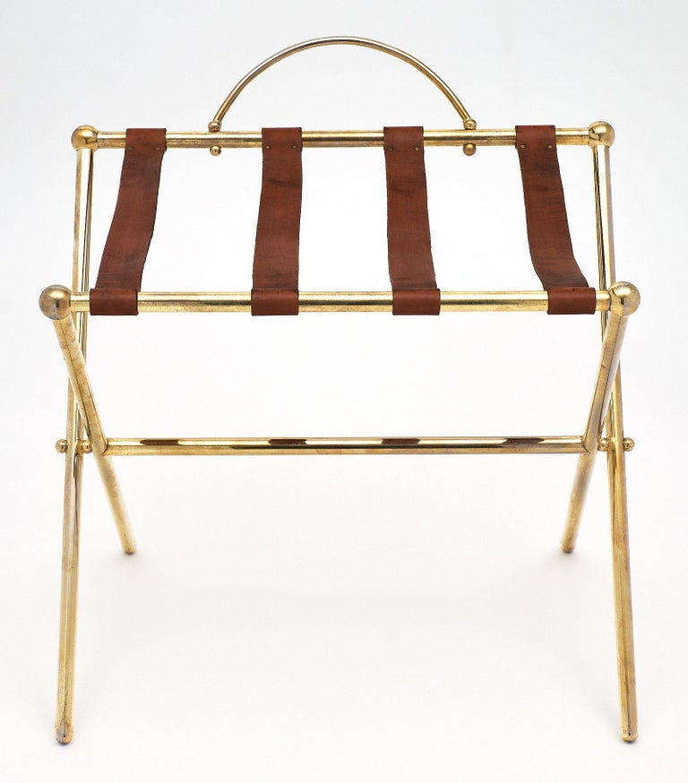 French vintage midcentury luggage stand. This luxury hotel luggage stand has a frame of brass and features leather straps. A wonderful accessory that adds character!