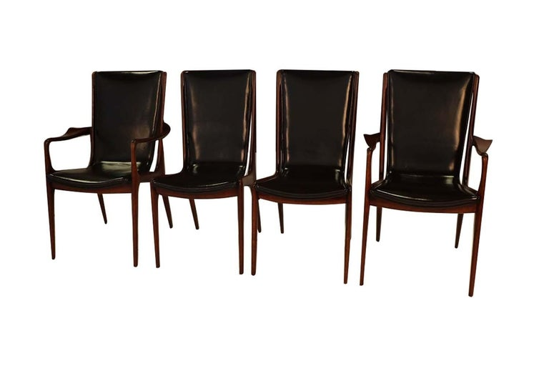 A beautiful rare set of four American walnut, Vladimir Kagan sculpted sling dining chairs, in black leather. This spectacular set of American walnut dining chairs consists of two VK 101 side chairs, and two VK 101A arm chairs. Signed with branded
