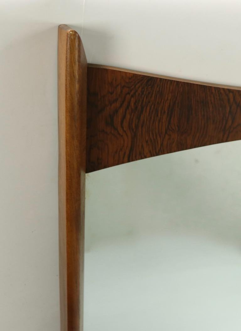 Mid Century  rosewood and walnut wall hanging mirror. The frame has an interesting crown form top creating a stylish architectural detail. The mirror is in clean, original condition, ready to hang.  Currently configured to hang with decorative form