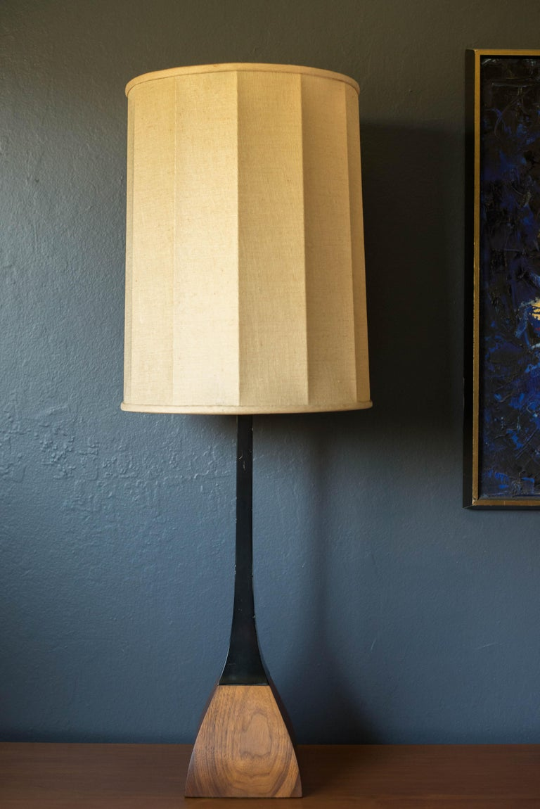 Vintage accent table lamp by Laurel Lamp Co. circa 1960s. This piece features a black stem and sculptural walnut base. Lamp shade is not included.      Offered by Mid Century Maddist