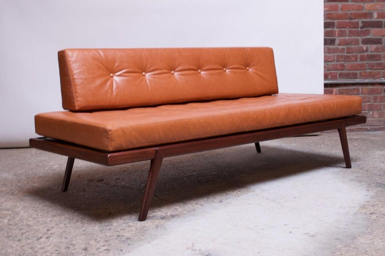 Daybed / settee designed by Mel Smilow for Smilow-Thielle in the 1950s. Solid walnut construction with newly upholstered Ralph Lauren leather cushions featuring button-tufted detail. Additionally, a Ralph Lauren brown suede lining has been fitted to