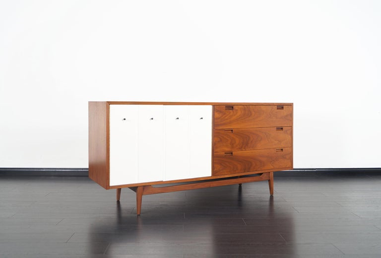 Beautiful Mid-Century Modern walnut credenza designed and manufactured by American of Martinsville in the United States, circa 1960s. Features a total of six dovetailed drawers, three drawers are hidden behind white lacquer Bi-Folding doors. The