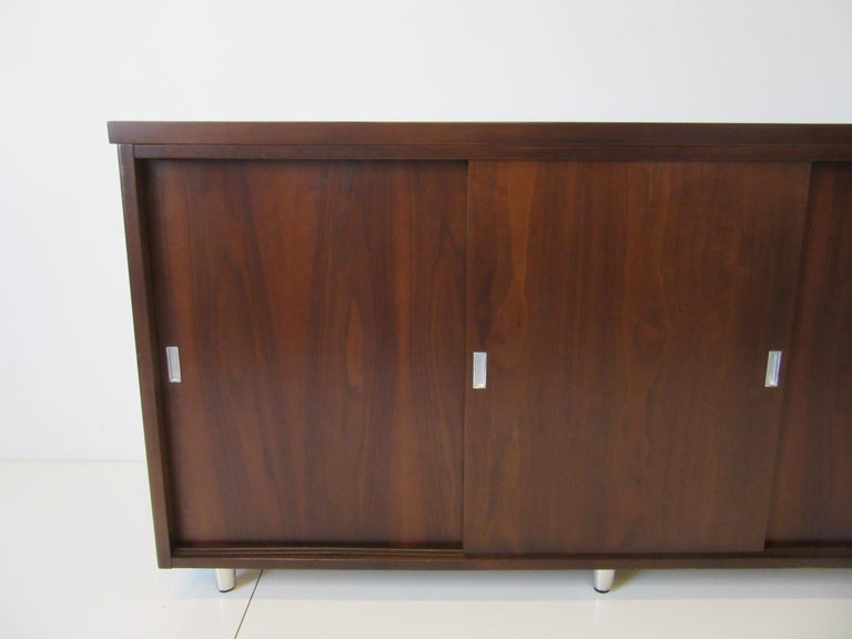 A dark walnut three sliding door credenza with four storage compartments, aluminum pulls and brushed aluminum legs having adjustable foot pads. The piece has a higher profile which is hard to find in a midcentury credenza, very well constructed