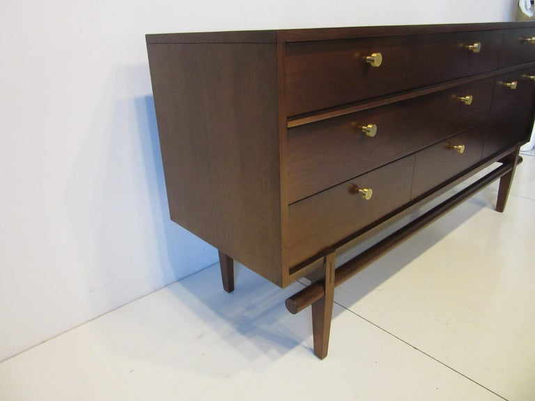A medium toned walnut finished dresser / chest with six drawers, two full sized, three single and one larger drawer having heavy brass pulls. There's a darker wood inset to the upper leg and rounded stretcher design giving this piece an outstanding