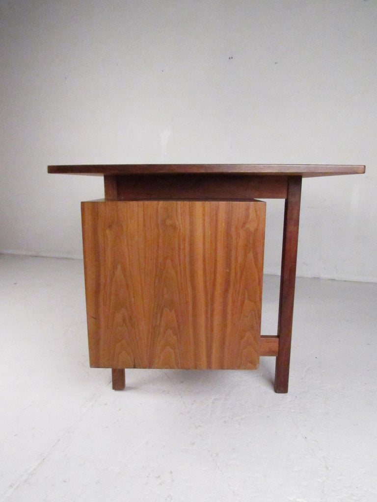 A beautiful vintage modern desk with a floating tabletop and a double pedestal base. The unique design boasts six hefty drawers ensuring plenty of room for storage. A well-made midcentury case piece with a finished back, conical drawer pulls, and a