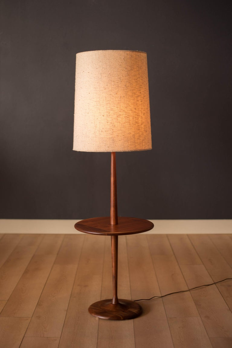 Vintage floor lamp with attached round side table by Laurel Lamp Co. circa 1960s. This piece is made of solid walnut and functions with a three-way switch. Drum shade is not included.   End table height 20.75