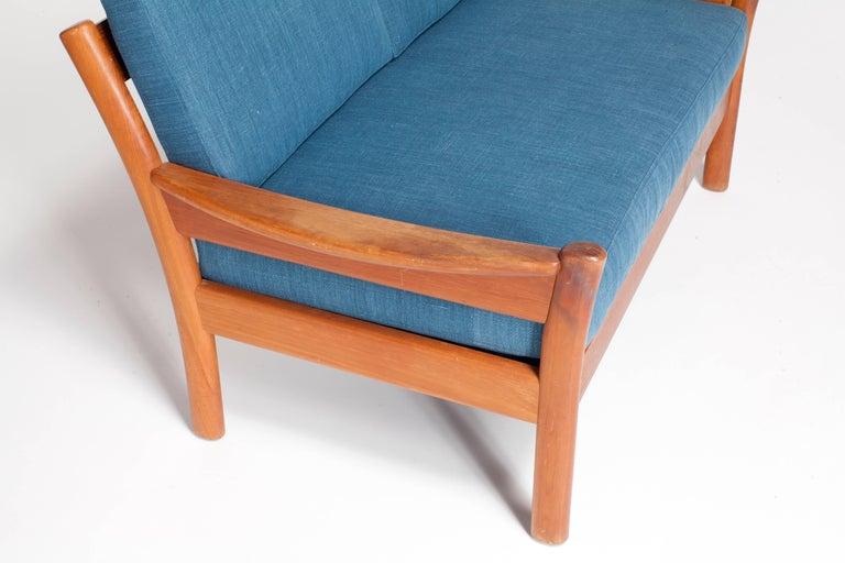 Midcentury walnut open framed settee upholstered in blue linen.