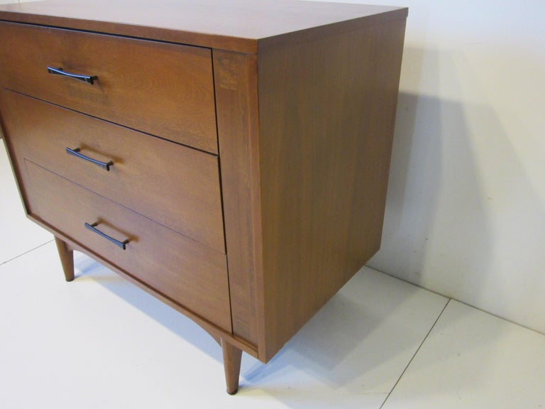 A smaller sized three-drawer commode / chest / dresser in a medium colored walnut with inlaid burl details to each side of the piece and having dark rich rosewood bow tie pulls with brass. Retains the manufactures branded mark by the Kroehler