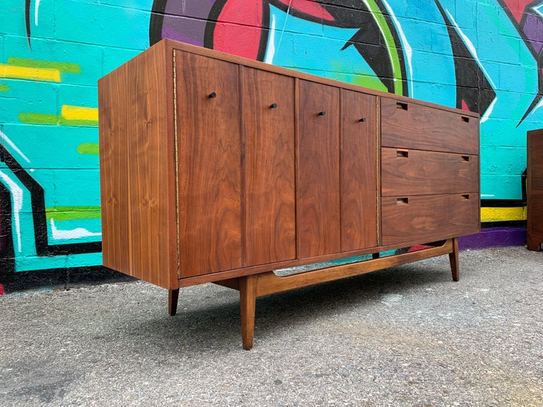 Vintage midcentury walnut sideboard credenza by American of Martinsville. Brilliant storage with 2 fold outdoors. Newly restored in excellent condition.