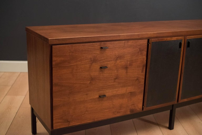 Mid-Century Modern dresser in walnut. This piece includes nine storage drawers with black metal pulls. Swing out doors are lined with black vinyl. Matching nightstands and tall dresser available in separate listing.