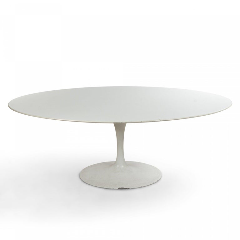 Midcentury white tulip dining table with white oval resin top and white metal pedestal base (EERO SAARINEN FOR KNOLL).