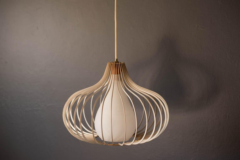 Vintage hanging wire pendant lamp circa 1960s. This piece has a frosted white teardrop glass pendant and walnut stem surrounded in a contoured metal frame.