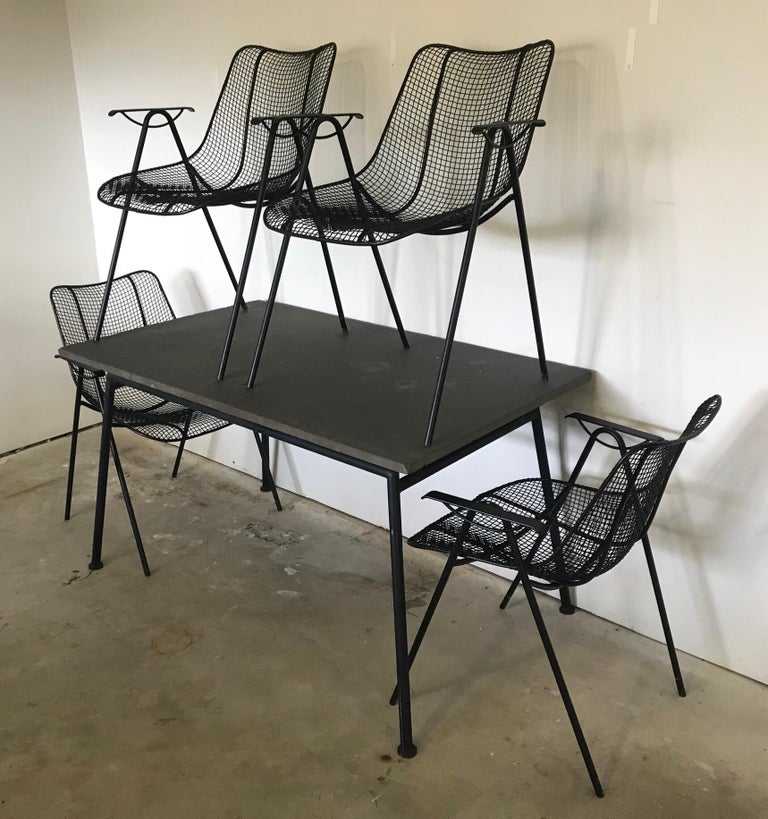 Very rare original slate top patio or poolside table by Woodard, wrought iron base accompanied by four chairs.