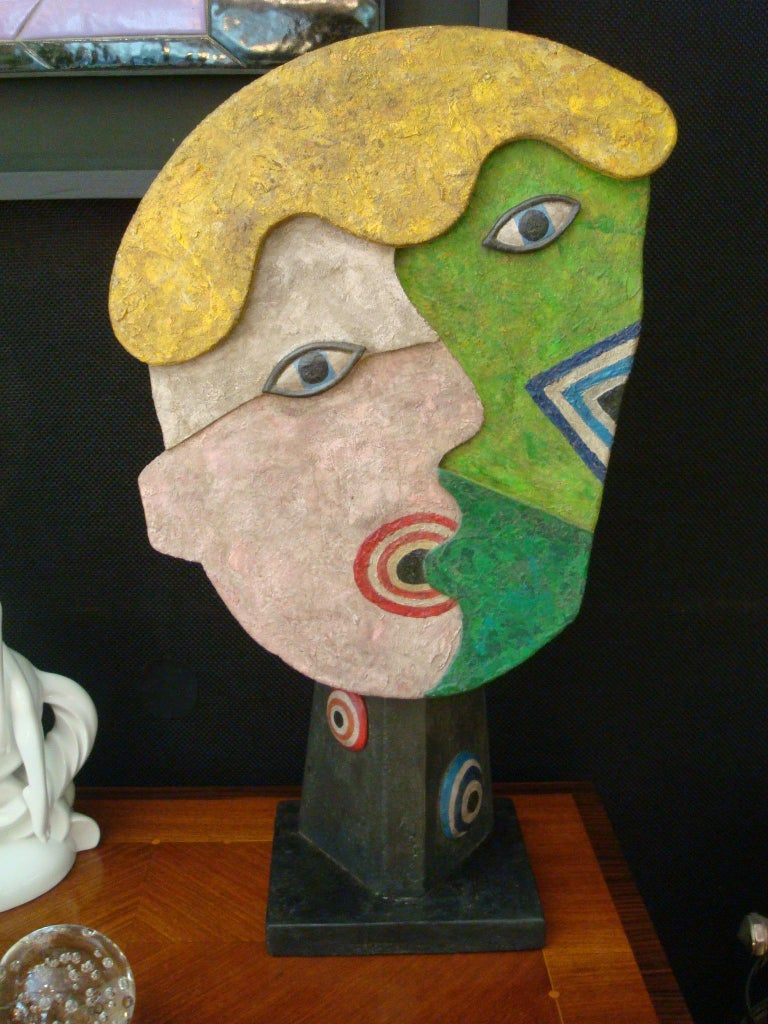 Painted wooden faces over a stand. Rare sculpture of the people talking. Nice colors. It has no signature.
