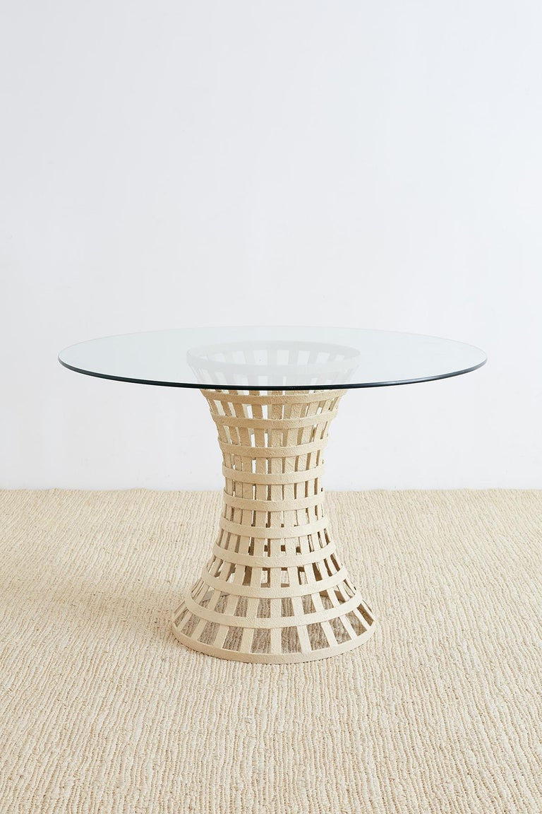Unique Mid-Century Modern woven metal basket style breakfast or dining table. Features a painted metal base constructed from metal rings and slats in a waisted form topped with a pane of round glass. The base is heavy and solid finished with a thick