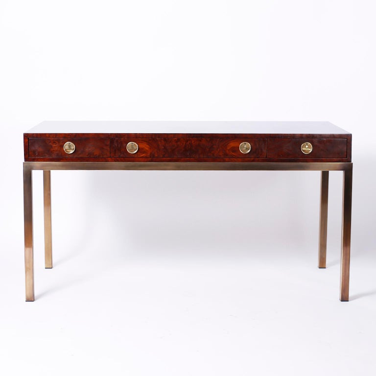 In vogue three-drawer writing desk with a lush custom finish over well grained burled walnut on all four sides, stylized brass Campaign hardware and elegant lacquered brass legs. Signed Mastercraft in a drawer.
