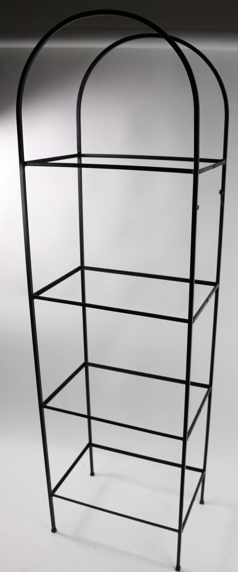 Arch top wrought iron shelf with plate glass shelves, attributed to Arthur Umanoff. Freestanding unit with four shelves, each 17 in apart. Great for display, storage etc. clean, ready to use.