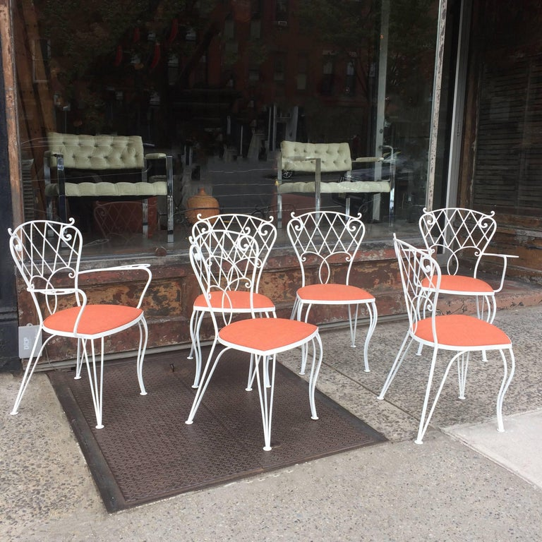 Set of six, mid century, patio, garden, outdoor, dining chairs feature scrolled, wrought iron frames that are newly painted with seats newly upholstered in durable outdoor fabric. The set includes four side chairs and two captain chairs that are