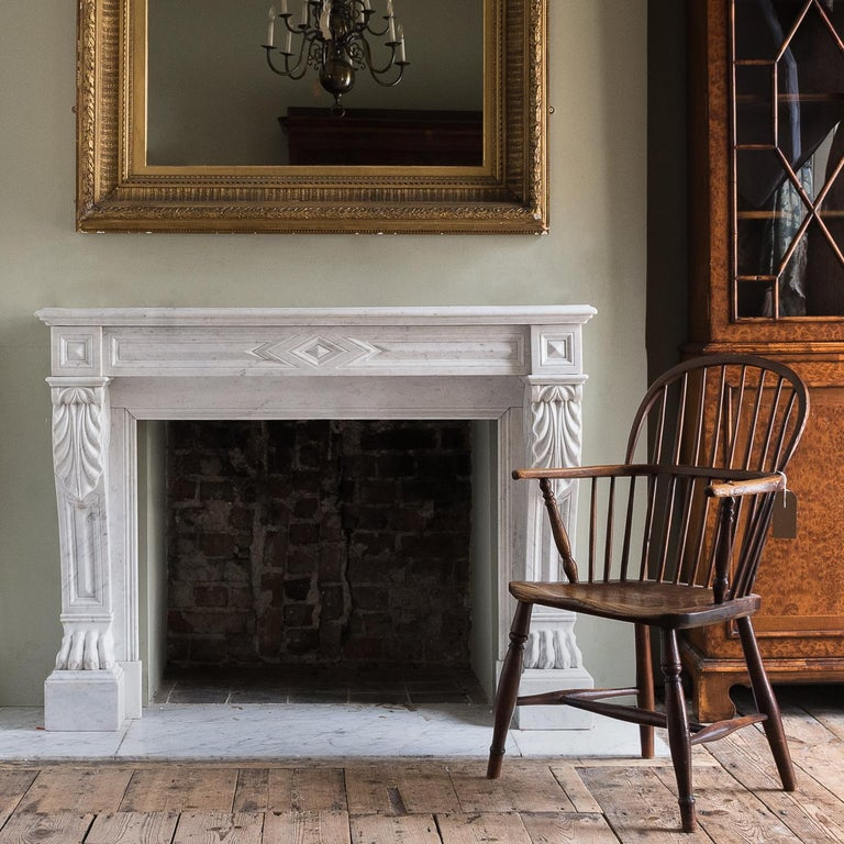 Mid-19th century French Empire style Carrara marble chimneypiece, the moulded rectangular shelf above frieze centred by diamond motif, the acanthus, scrolled and panelled jambs with lion's paw feet.