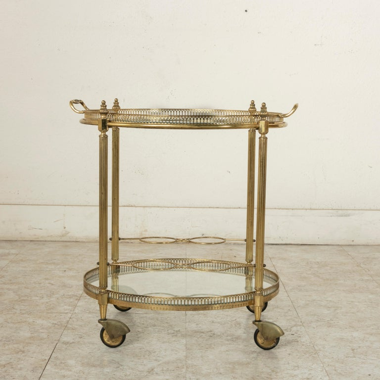 This mid-20th century French round brass bar cart features fluted legs finished with Louis XVI inspired finials and two glass shelves surrounded by a pierced bronze gallery. The upper shelf also serves as a removable serving tray with two handles to