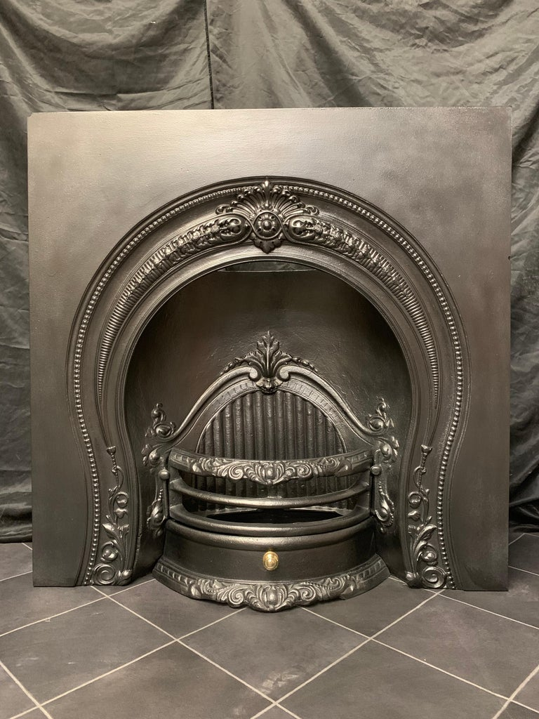 A generous sized Mid Victorian Horseshoe style arched cast iron fireplace insert, a large outer plate with a decorative central cartouche with curved horns following the contour of the horseshoe opening, the internal curved fire back with reeded
