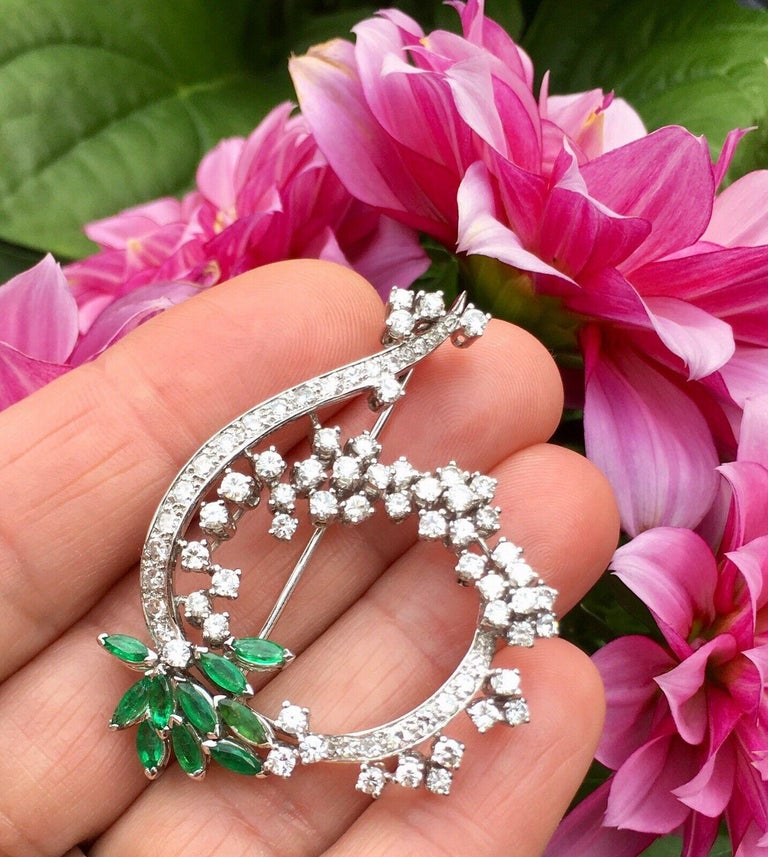 This gorgeous large brooch measures 38mm wide x 52mm in length and is set with high quality VS near colorless white diamonds, totaling approximately 2.00 carats in diamonds alone.  The brooch is further set with marquise shaped green lively emeralds