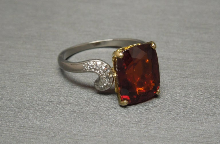 In a Midcentury design, featuring a central GIA Certified 8.80 carat Cushion cut Natural Rich Red Garnet, secured in an 18 Karat Yellow Gold 4-Prong Fleur de Lis setting, with a Platinum shank. [The Fleur de Lis symbol in jewelry is attributed to