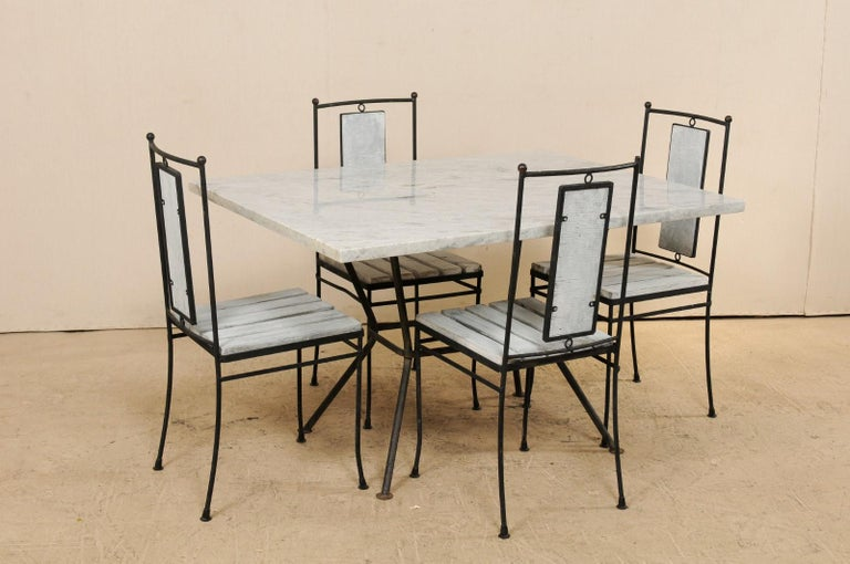 This midcentury American dining set includes a marble-top table with four side chairs. The rectangular-shaped table features a newer, pale grey marble top which rests atop a black iron frame comprised of four legs which cant inward toward the center