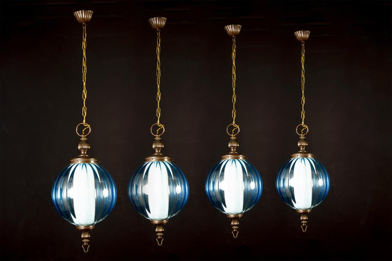 A rare set of four midcentury aquamarine color Murano glass atmosphere lights or lanterns. Inside each with a E 27 light bulb covered by a refined ribbed opaline glass, creating a fabulous light effect. Attributed to Luigi Caccia Dominioni. Each