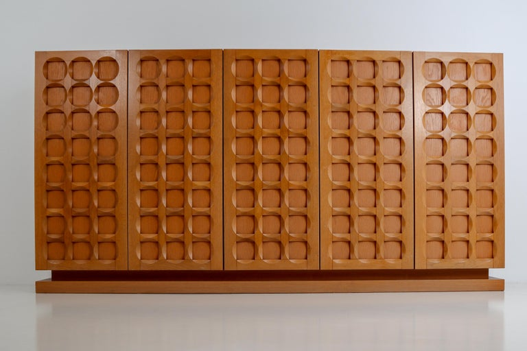 Belgium oak Brutalist credenza equipped with four door panels that show a high quality wood carvings in a beautiful graphic pattern, consisting out of circles and squares that give this sideboard a strong and impressive appearance. The top part is