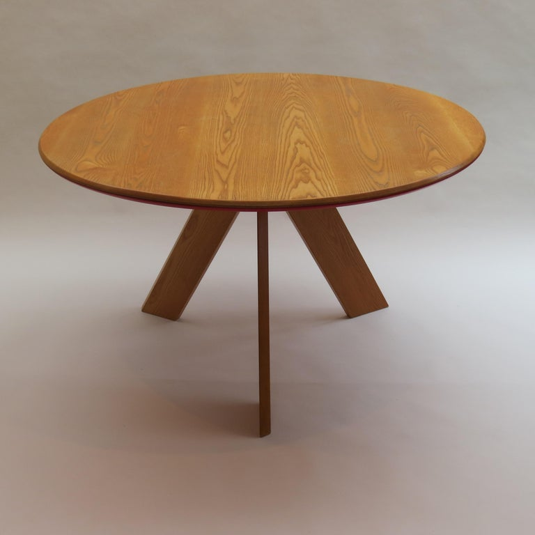 A very nicely detailed and good quality round dining table designed and produced by David Field. Bespoke made in solid ash base with blue aluminum Bose on the underside. The solid ash circular top has a painted red MDF to the underside.