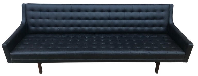 Beautiful unique Mid-Century Modern black faux leather vinyl tufted sofa with walnut wood base and leather by Patrician. Very soft ribbed black faux leather with texture on hardwood walnut frame and simple structure. Low seating 15