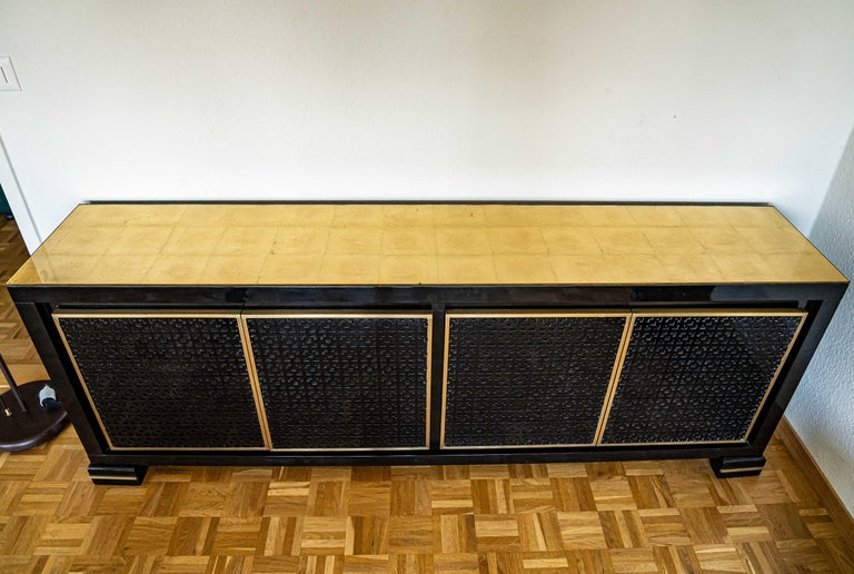 Midcentury black lacquered credenza with a sets of drawers and shelves, red lacquered inside. Gold leaf glass top.
