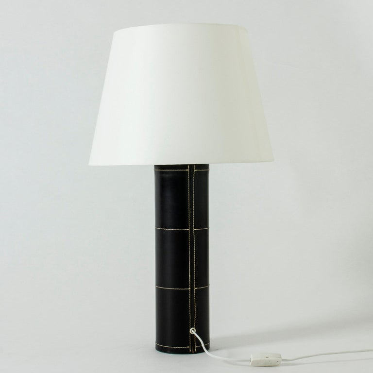 Large table lamp from Bergboms with a cylinder base dressed in black leather. Decorated with white seams – a Minimalist design with a deluxe finish.