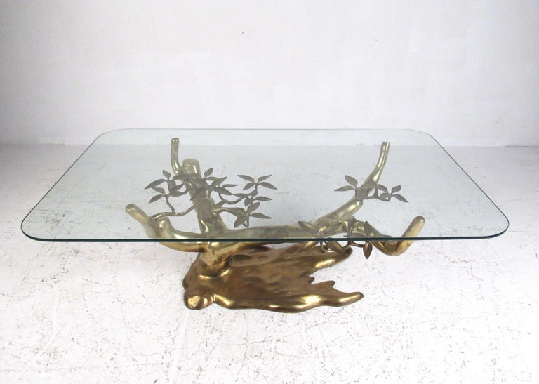 This stunning midcentury cocktail table features a sculptural brass