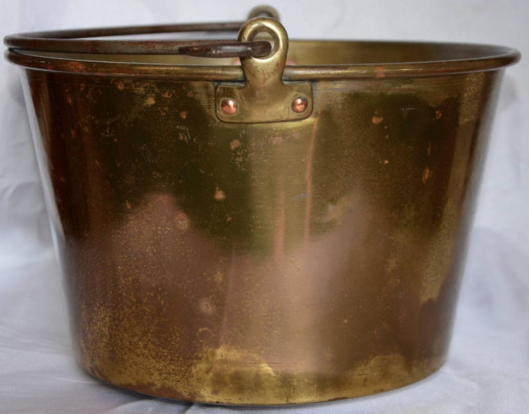 You can tell this brass bucket was used at some time for a special purpose. The dents on the bottom are attempting to tell a story. The cast iron handle is held in place with brass loops that are attached to the bucket with copper brads. This would