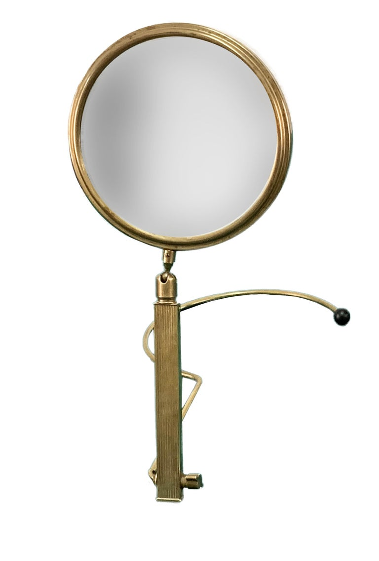Beautiful midcentury brass table mirror, the article was produced in France during the 1950s.  This amazing piece is made of brass with an adjustable two-sides stand.  It is a wonderful item, ideal for a bathroom or a midcentury bedroom. There